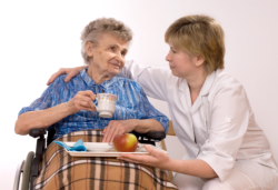 caregiver assisting old woman in eating